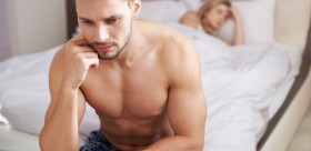 man on side of bed looking stressed