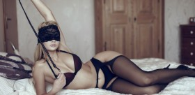 Sexy woman in blindfold on bed