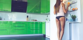 Full length back view of beautiful sexy girl in underwear smiling while getting an orange from fridge in the kitchen
