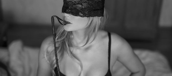 Sexy blonde woman with lace eye cover and whip black and white, bdsm